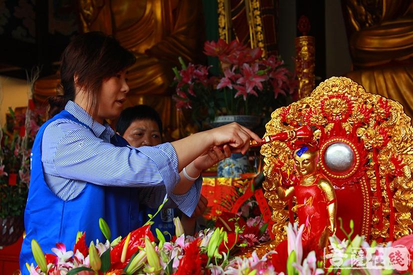 义工以圣水沐浴释迦太子圣像(图片来源:菩萨在线 摄影:慧德)