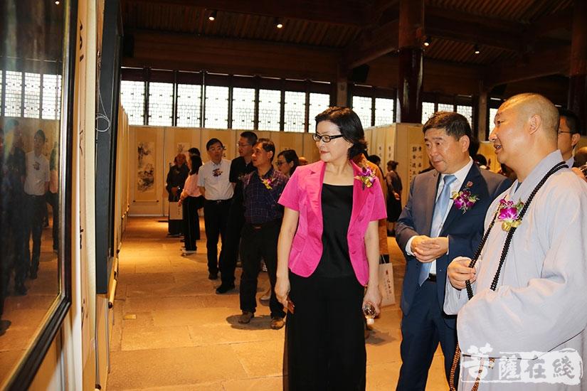 印超法师陪同嘉宾参观书法展(图片来源:菩萨在线 摄影:妙月)