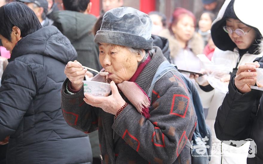 老人品尝腊八粥(图片来源:菩萨在线 摄影:妙月)