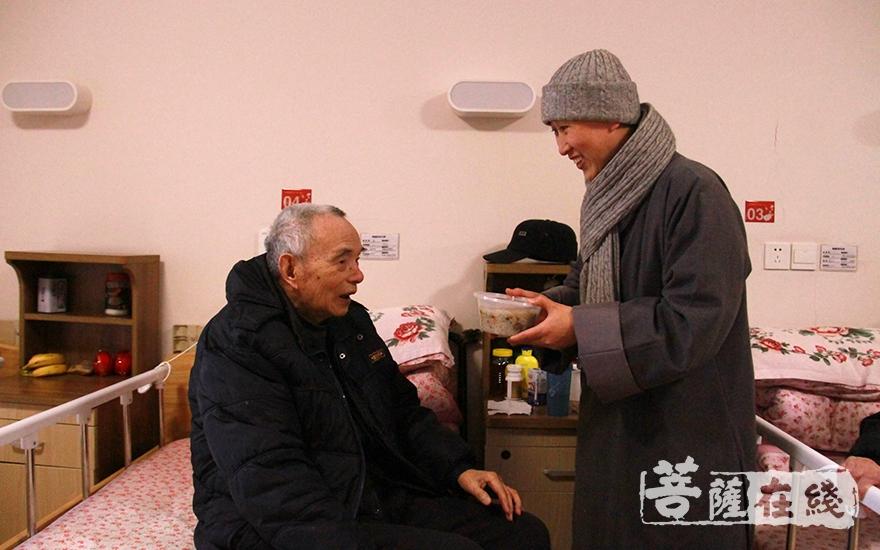 把热气腾腾的腊八粥送到老人手里(图片来源:菩萨在线 摄像:妙微)