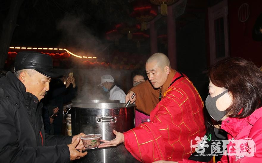 盖忠法师为信众盛上热气腾腾的腊八粥(图片来源:菩萨在线 摄影:妙月)