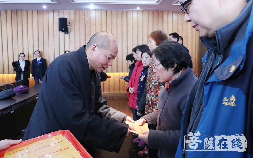 长春法师为困难群众发放慰问金(图片来源:菩萨在线 摄影:妙月)