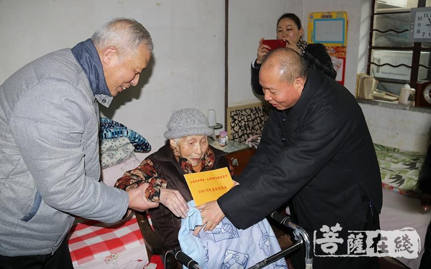 为老人送上慰问金(图片来源:菩萨在线 摄影:妙月)