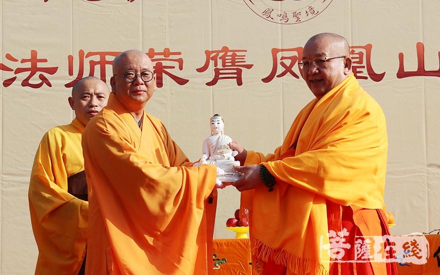 中国佛教协会副会长、西双版纳总佛寺住持?#20102;?#21015;龙庄勐长老授佛像(图片来源:菩萨在线 摄影:妙月)