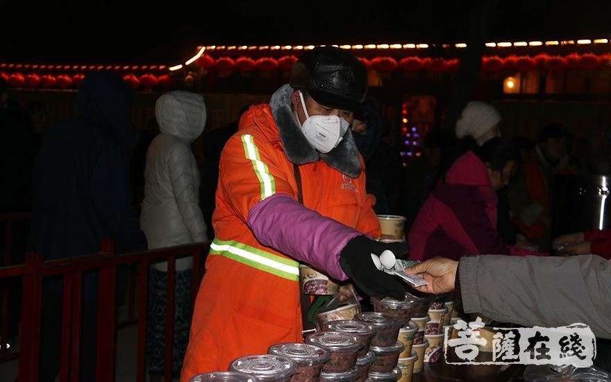 环卫工人排队领腊八粥(图片来源:菩萨在线 摄影:妙月)