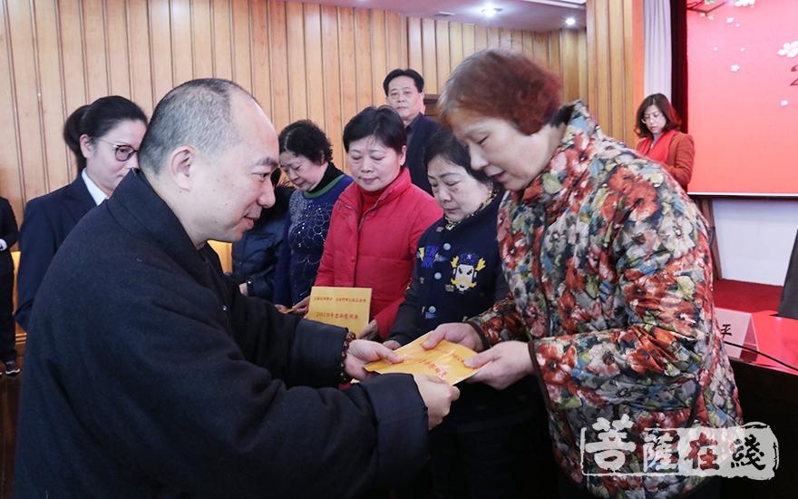 慧觉法师为困难群众发放慰问金(图片来源:菩萨在线 摄影:妙月)