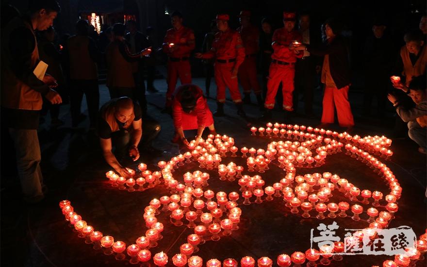 义工摆放莲花灯(图片来源:菩萨在线 摄影:唐雪凤)