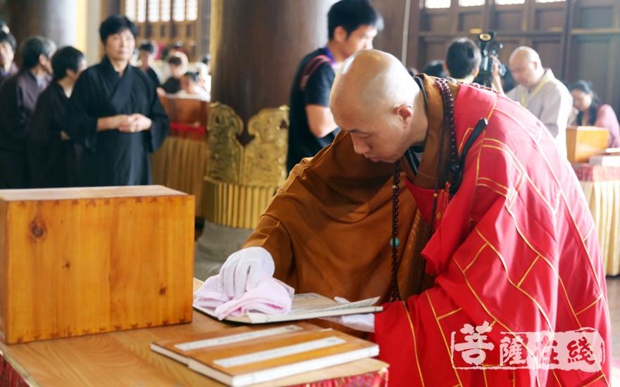 怡藏大和尚取出经书并小心擦拭(图片来源:菩萨在线 摄影:李蕴雨)