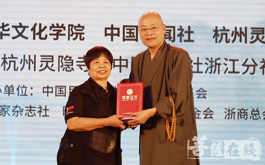 光泉法师为陈树菊颁发荣誉证书(图片来源:菩萨在线 摄影:邓彬)